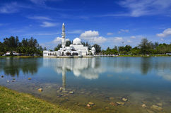 Beautiful white mosque with reflection in the lake during clean blue sky Stock Photography