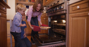Beautiful white mother using oven mitts to remove cookie tray Royalty Free Stock Photography