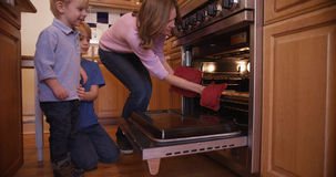 Beautiful white mother using oven mitts to remove cookie tray Stock Photo