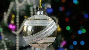 Beautiful white New Year and Christmas decoration ball swinging on rope. Against a background of a rotating Christmas tree and a flashing garland stock footage