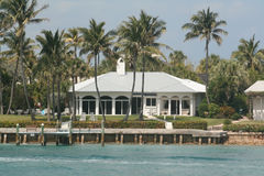 BEAUTIFUL WHITE OCEANFRONT HOME WITH A DOCK. WHITE OCEANFRONT HOUSE, WITH A DOCK, ON A SUNNY, BLUE SKY DAY IN FLORIDA. PALM TREES,  & BLUE WATER MAKE FOR A Stock Image
