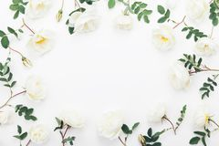 Beautiful white rose flowers and green leaves on table top view. Wedding frame in flat lay styling. Beautiful white rose flowers and green leaves top view Stock Photography