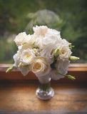 Beautiful white Roses in a glass vase near window. Stock Photography