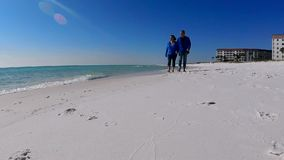 Beautiful white sand beach couple walkiing holding hands stock footage