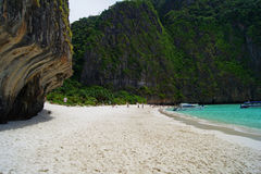 Beautiful white sandy beach beside the blue ocean surrounded by the treed rocks. Thailand. Beautiful white sandy beach beside the blue ocean surrounded by the Stock Photography