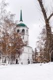 Beautiful white snowy path in the cold and winter leading to a church. A white church with green pointy roof under cloudy sky. All trees are in brown and their royalty free stock photo