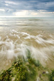 Beautiful white and soft wave flow over the rock and mossy hitti Stock Photography