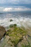 Beautiful white and soft wave flow over the rock and mossy hitti Stock Images