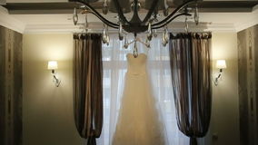 Beautiful white stylish wedding dress on hanger on the background of a window in lluxury apartments stock video footage
