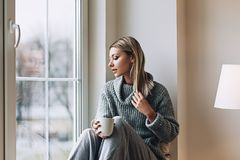 Beautiful white stylish woman in cozy scandinavian interrior sits at home near the big window, portrait of the beautiful. Girl, fashion portraits, woman with stock images