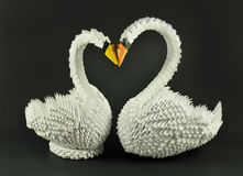 Beautiful white swans origami. Beautiful white handmade swans origami in love, isolated on black background, with the necs forming a heart shape Stock Photo