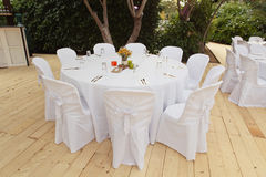 Beautiful white table and chairs in restaurant. Wedding party setting with white draperies stock photo