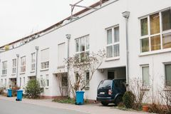 Beautiful white two-storey house with bushes and garbage cans and parked car. Germany. Stock Images