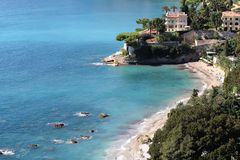 Beautiful white villa by sea. Monte Carlo, Monaco - September 20, 2015: beautiful white villa seen from above shingle beach line blue sea and green trees water Royalty Free Stock Images