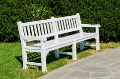 Beautiful white vintige bench in park. Vintage bench in park painted in white stock photo