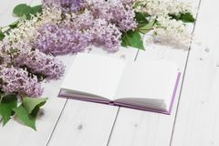 Beautiful lilac branch with note-book on the wooden background Royalty Free Stock Photography