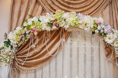Beautiful white wedding arch decorated with pink and red flowers Royalty Free Stock Images