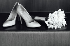 Beautiful white wedding bouquet of lilies lies next to the bride`s shoes.  Royalty Free Stock Photos