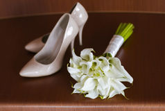 Beautiful white wedding bouquet of lilies lies next to the bride`s shoes.  Stock Photo