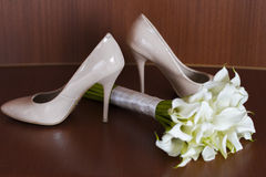 Beautiful white wedding bouquet of lilies lies next to the bride`s shoes.  Stock Image