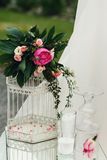Beautiful white wedding cage decoration with flowers and leaves Stock Photo