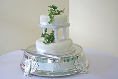 Beautiful White Wedding Cake. A beautiful white wedding cake, complete with a silver pedestal and knife with decorations Stock Photo