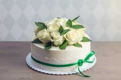 Beautiful white wedding cake decorated with bouquet of flowers white roses. Concept of elegant holiday desserts. Beautiful white wedding cake decorated with Stock Photos