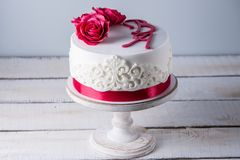 Beautiful white wedding cake decorated with flowers red roses and ribbon. Concept of elegant holiday desserts