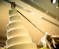 Beautiful white wedding cake. Figurines of the bride and groom on a wedding cake.Funny figurines suite at a luxury wedding white cake decorated .Figurines on top royalty free stock photography