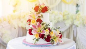 Beautiful white wedding cake with red roses as decoration. Royalty Free Stock Photos
