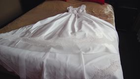 Beautiful white wedding dress of the bride lies on a huge bed. 1 stock video footage