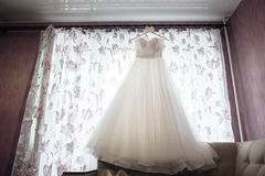 Beautiful white wedding dress on hanger on the background of a window. Beautiful white luxury wedding dress on hanger on the background of a window Royalty Free Stock Image