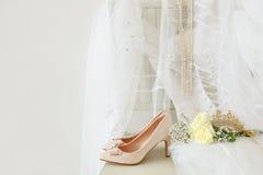 Beautiful white wedding dress, shoes, gold diamond tiara and veil on chair Royalty Free Stock Photo
