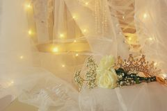 Beautiful white wedding dress, tiara and veil on chair with gold garland lights Stock Image