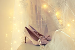 Beautiful white wedding dress and veil on chair with gold garland lights Stock Image