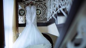 Beautiful White Wedding Gown Hanging by Window stock video footage