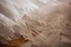 Beautiful white wedding veil with lace. Lies on the bed Royalty Free Stock Photography
