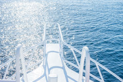 Beautiful white yacht bow on water background. Beautiful white yacht bow on blue water surface background Royalty Free Stock Photo