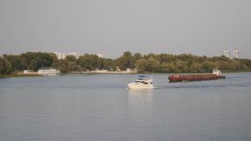 Beautiful white yacht floating on river. Small white boat and old rusty barge sail on river. stock video footage
