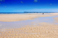 Beautiful wide open sandy beach over looking jetty pier Stock Images