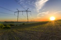 Beautiful wide panorama of high voltage lines and power pylons stretching through quiet green spring fields and forest at dawn or stock photography