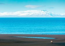 Beautiful wide shot of the sea with amazing white mountain in the background royalty free stock photography