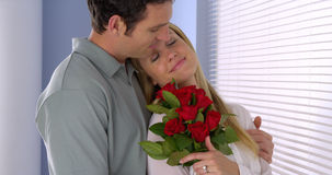 Beautiful wife gets surprised with bouqet of roses Royalty Free Stock Image
