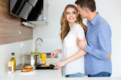 Beautiful wife making pancakes and flirting with husband Royalty Free Stock Images