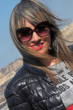 Beautiful wife, salt & pepper hair, the wind in your hair. Sunny day on the roof of the building. Glasses on the face, the wind mo Royalty Free Stock Images