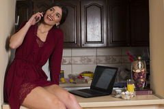 Beautiful wife talking on a phone at home Royalty Free Stock Images
