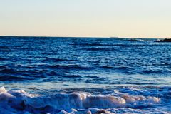 Beautiful wild beach with azure sea, waves on the shore in Tuscany, Italy. Sunny day at the beach royalty free stock image