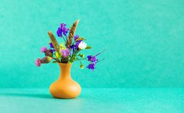 Beautiful wild flowers bouquet, brown clay vase on green background. Summer time floristic still life photo. Shallow stock photography
