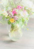 Beautiful wild flowers bunch in glass vase on light background, soft focus, close up. Royalty Free Stock Photography