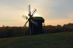 Beautiful windmill with a green roof on a meadow near the forest Stock Photos